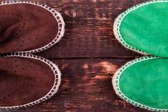 Chaussures vertes et brunes d'espadrille de suède sur le fond en bois Image stock