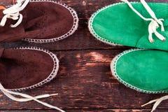 Chaussures vertes et brunes d'espadrille de suède sur le fond en bois Images stock