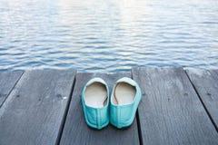 Chaussures vertes sur le passage couvert en bois avec de l'eau dans l'avant photographie stock libre de droits