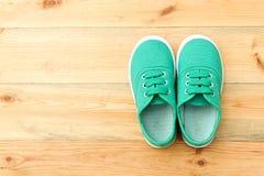 Chaussures vertes sur le plancher en bois Photo stock