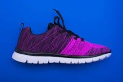 Chaussures violettes et noires de femme de sport d'isolement sur le fond bleu Photos stock