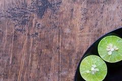 Chaux dans le plat noir sur la table en bois Images stock