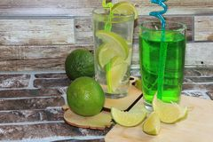 Chaux en gobelets et fruit en verre avec la menthe sur une table en bois photos stock