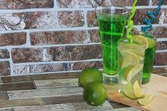 Chaux en gobelets et fruit en verre avec la menthe sur une table en bois photo libre de droits