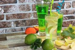 Chaux en gobelets et fruit en verre avec la menthe sur une table en bois images stock
