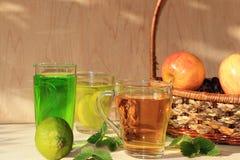 Chaux en gobelets et fruit en verre avec la menthe sur une table en bois image libre de droits