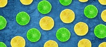 Chaux et citron juteux d?coup?s en tranches sur un fond bleu-fonc? concret Fruits frais Fond de fruit Nourriture saine Vitamines  images libres de droits