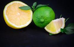 Chaux et citron mûrs et juteux avec un brin de menthe sur une étiquette foncée photographie stock libre de droits