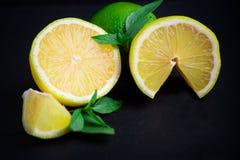 Chaux et citron mûrs et juteux avec un brin de menthe sur une étiquette foncée photographie stock