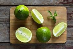 Chaux et menthe sur le panneau de cuisine Chaux, fruits entiers et tranches découpées en tranches Photos libres de droits