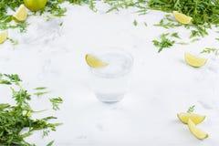 Chaux fraîches dans l'eau sur un fond blanc Verts et tranches de chaux à l'arrière-plan Une glace de l'eau avec la limette Image libre de droits