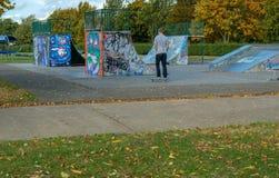 Chaval joven en el parque del patín alrededor a comenzar a practicar Imagen de archivo