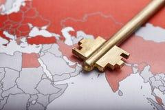 A chave à porta no mapa do mundo imagens de stock royalty free