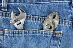 Chave ajustável e alicates no bolso de calças de ganga Imagem de Stock