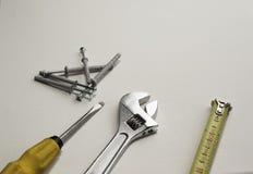 Chave ajustável, régua, chave de fenda e parafusos em um fundo branco Fotos de Stock