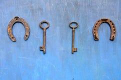 A chave antiga oxidada e a ferradura penduram na parede de madeira do celeiro fotografia de stock royalty free