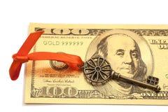 Chave ao sucesso com curva vermelha em cem notas de dólar dourada Fotografia de Stock