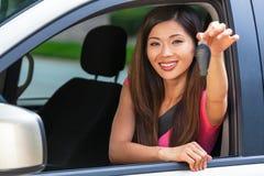 Chave asiática chinesa da terra arrendada da menina da jovem mulher que conduz o sorriso do carro imagens de stock royalty free