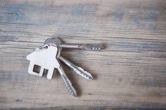 Chave com ícone da casa no fundo de madeira Imagem de Stock Royalty Free