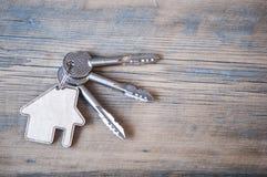 Chave com ícone da casa no fundo de madeira Foto de Stock