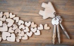 Chave com ícone da casa no fundo de madeira Fotos de Stock Royalty Free
