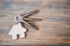 Chave com ícone da casa no fundo de madeira Imagens de Stock Royalty Free