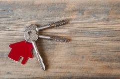 Chave com ícone da casa no fundo de madeira Fotografia de Stock Royalty Free
