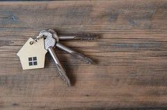Chave com ícone da casa no fundo de madeira Foto de Stock Royalty Free