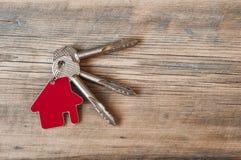 Chave com ícone da casa no fundo de madeira Imagem de Stock