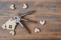 Chave com ícone da casa no fundo de madeira Fotos de Stock
