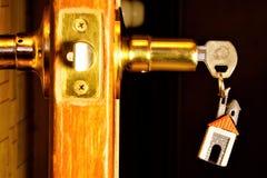 Chave com um keychain sob a forma de uma casa na fechadura da porta A ferramenta chave aos fechamentos abertos para indícios, sol imagem de stock