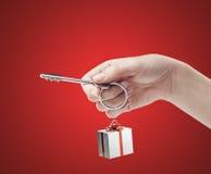 Chave da terra arrendada da mão com um keychain Imagens de Stock