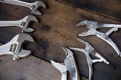 A chave de chave ajustável ou de chave inglesa e os alicates de travamento no fundo de madeira, preparam ferramentas básicas da m Imagem de Stock