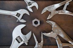 A chave de chave ajustável ou de chave inglesa e os alicates de travamento no fundo de madeira, preparam ferramentas básicas da m Fotos de Stock