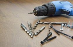 Chave de fenda e brocas elétricas azuis no assoalho imagem de stock