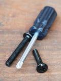 chave de fenda e parafuso no fundo de madeira Imagem de Stock Royalty Free