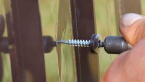 Chave de fenda e parafusos da mão cortados na opinião do fim da chapa metálica do ferro As mãos dos homens que reparam a cerca filme