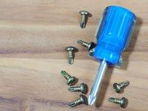 chave de fenda e parafusos no fundo de madeira Fotografia de Stock