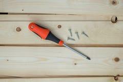 Chave de fenda e parafusos sobre as placas de madeira Fotografia de Stock Royalty Free