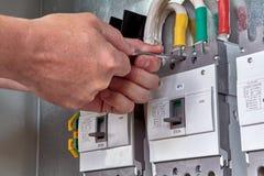A chave de trabalho do homem parafusa o interruptor à placa de circuito fotografia de stock