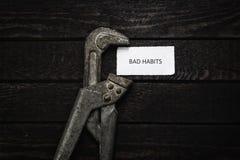 A chave de tubulação comprime um pedaço de papel com hábitos maus de uma inscrição Pare hábitos maus HDR filtrou e tonificou a im fotografia de stock royalty free