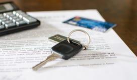 Chave do carro, cartão de crédito em um contrato de vendas assinado Imagem de Stock