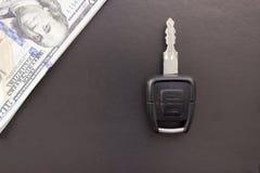 Chave do carro e dólares, fundo preto, dólar da compra imagem de stock