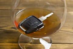 Chave do carro em um vidro com perigo do álcool fotografia de stock