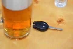 A chave do carro encontra-se em uma tabela perto dos vidros do álcool Imagem de Stock Royalty Free