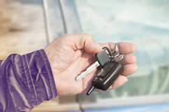 Chave do carro na mão do ` s do homem em um fundo do carro toned Mão idosa do ` s do homem Autumn Colors fotografia de stock royalty free