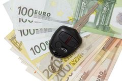 Chave do carro no fundo do dinheiro do Euro isolado no fundo branco Fotografia de Stock Royalty Free