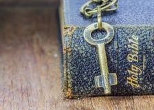 A chave do metal na Bíblia Sagrada na tabela de madeira Imagens de Stock Royalty Free