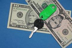 Chave e dólares no fundo azul Foto de Stock Royalty Free