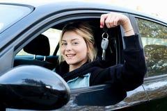Chave guardando feliz do carro da moça assentada em seu carro novo Fotos de Stock